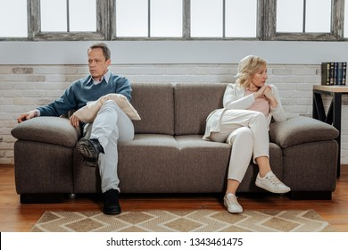 Wife sitting nearby. Distressed short-haired man sitting far away from his upset wife while visiting family psychotherapist