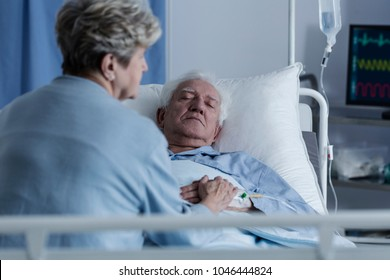 Wife sitting on a hospital bed by an elder man in a coma