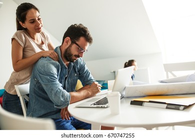 Wife tries to relax her husband with massage.He is very tense and tired after work on his new project.Working at home concept.