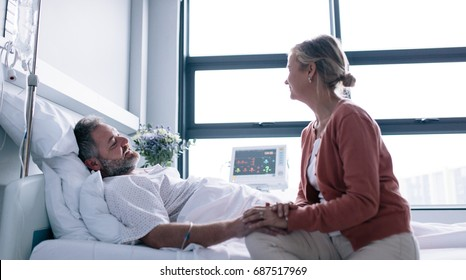 Wife visiting husband in hospital. Woman consoling hospitalised man.