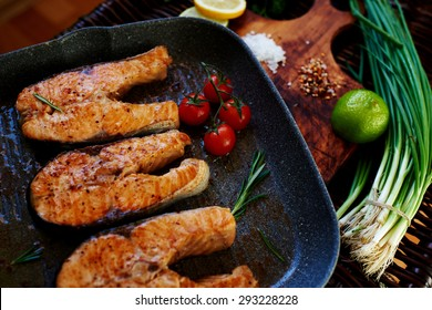 Wife waits for guests to cook for dinner salmon steaks,Fish steaks are on the grill pan with rosemary and tomatoes,On a wooden board with a pan put the fried fish
