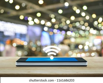 wi-fi button flat icon on modern smart phone screen on wooden table over blur light and shadow of mall, Technology and internet concept