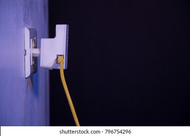 WiFi extender in electrical socket on the wall with ethernet cable plugged in. The device is in access point mode that help to extend wireless network in home or office.