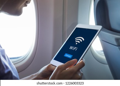 Wifi internet access in airplane during flight, passenger using tablet computer to connect to wireless network technology onboard to read email while flying