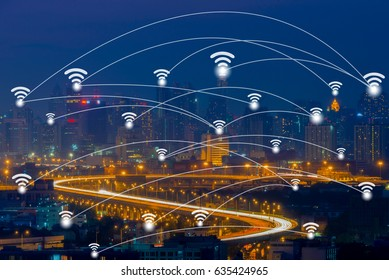 Wifi network connection concept on aerial view of cityscape business district at twilight background.