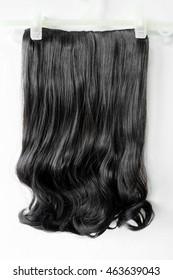 Wig of dark hair on a white background