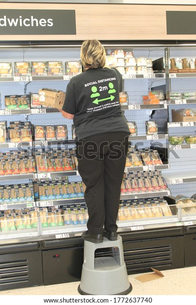 Wigan Manchester, UK, 09/07/2020: female shop worker stacking shelves wearing a black and green social distancing t-shirt