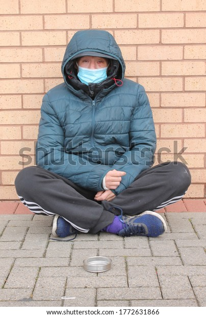 Wigan, Manchester, UK, 09/07/2020: Homeless women with bruised eye, wearing a blue mask sitting on the floor with legs crossed begging for change