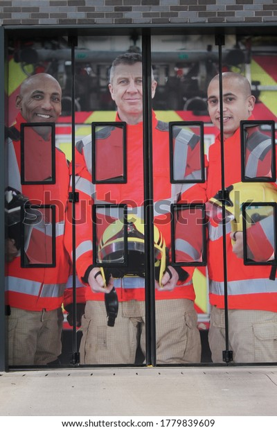 Wigan, Manchester, UK, 20/07/2020: three male fire fighters on the the entrance of electric folding doors for emergency vehicles