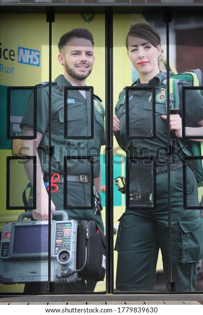 Wigan, Manchester, UK, 20/07/2020: Two emergency workers on the the entrance of electric folding doors for emergency vehicles in UK