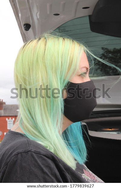 Wigan, Manchester, UK, 20/07/2020:  young lady side on view with dyed coloured hair wearing a black masking