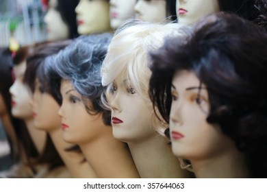 wigs on mannequin heads, a row of mannequins on a shelf in a wig shop