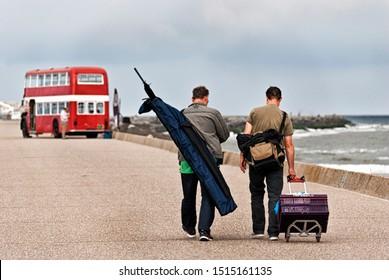 Wijk aan Zee, The Netherlands - 2016: Old English red double decker schoolbus in the background with fisherman walking towards it