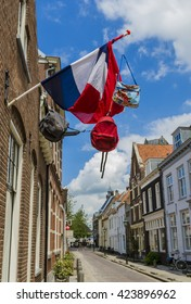 Wijk bij Duurstede, The Netherlands - June 17, 2012: Street with old houses and dutch flag with three bags.
