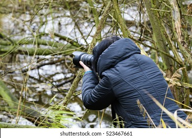 Wild animal photographer on a cold day with her camera on the way on motive search