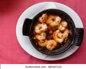 Wild argentine fried shrimps in hot olive oil with garlic and chili pepper in a black pan on white plate with red background