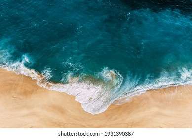 Wild beach with a beautiful clear ocean. Ocean from a bird's eye view. Top view of the tropical beach. Paradise island. Lonely sandy beach with beautiful waves. Beaches of Indonesia. Copy space
