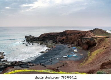 wild beach on the Atlantic Ocean in El Golfo village, Lanzarote. A rocky beach with fishing boats surrounded by volcanic mountains
