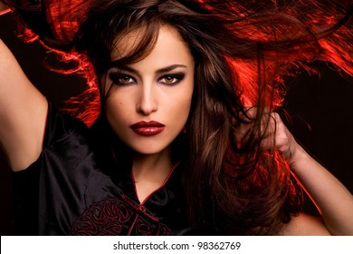 wild beauty with long flying hair and red back light, studio dark