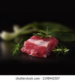 Wild black boar raw fillet prepared for grilling with rosemary shot against a black background. Copy space.