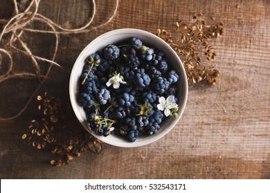 Wild Blackberry in white bowl on wooden background