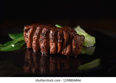 Wild Boar Fillet steak in iron skillet with Pak Choi. Selective focus and copy space. The perfect image for your bistro menu cover art.