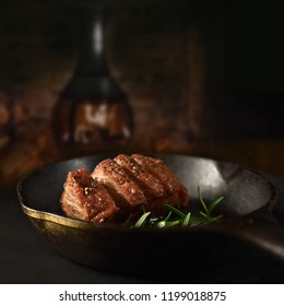 Wild Boar Fillet steak in iron skillet. Selective focus and copy space. The perfect image for your bistro menu cover art.