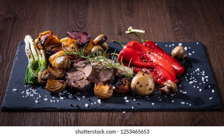 Wild boar grill with mix vegetables on a black stone