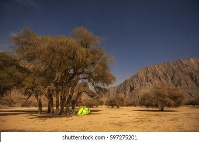 Wild camping in Musandam peninsula, Oman, Arabia, night photo with shining camping tent