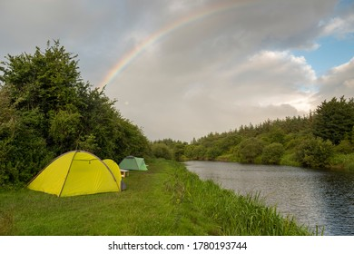Wild camping on the bank of the river with rainbow in the background. Ireland