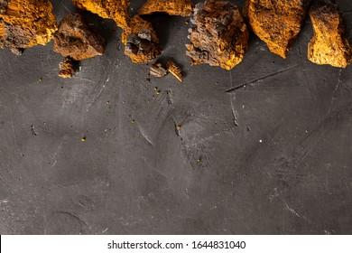 Wild Chaga Mushroom lives on birch bark, inonotus obliquus, on dark textured background. Top view. Ingredient for making tea, organic healthy hot drink, natural remedy, antioxidant. Copy space. Food