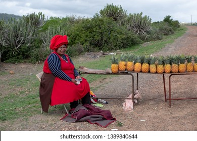 Wild Coast, South Africa. March 2019. Woman in red dress and hat sells pineapples by the roadside in rural Transkei, South Africa.