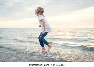 Wild emotions. Young and happy girl is jumping in the water at the beach