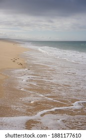 Wild empty beach with footsteps on the sand and ocean waves on the sand in Comporta, Portugal