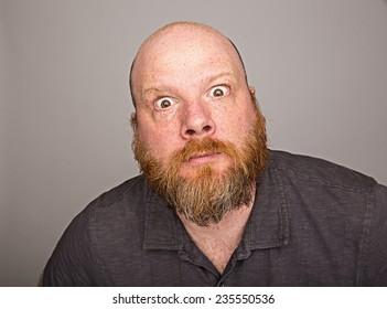 wild eyed bald man with full red beard