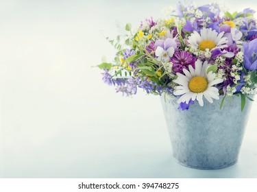 Wild flower bouquet on light blue vintage background