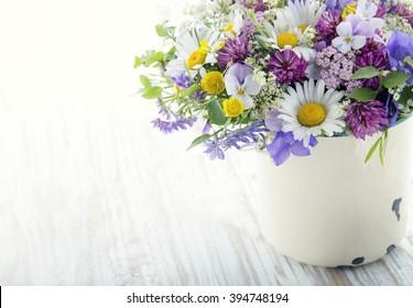 Wild flower bouquet on white vintage wooden background