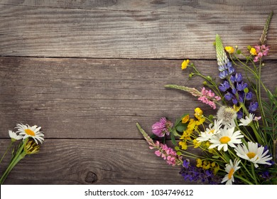 Wild flowers on old grunge wooden background (chamomile lupine dandelions thyme mint bells rape).