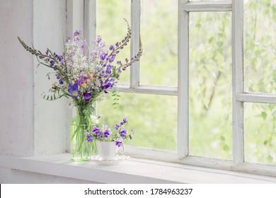 wild flowers in vase on white windowsill - Shutterstock ID 1784963237