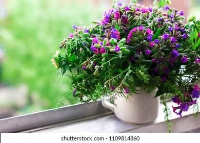 Wild forest meadow bouquet of cherry, lungwort, wild herbs in ceramic cup on window sill