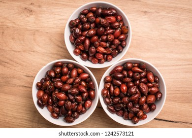 Wild fruit of rosehip for making rosehip tea in bowl on wooden table