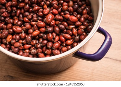 Wild fruit of rosehip for making rosehip tea in metal pot on wooden table