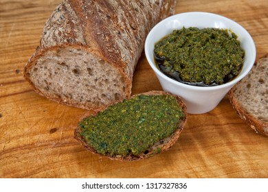 Wild garlic basil pesto in a white bowl and on a piece of bread together with a sliced baguette on a wooden background