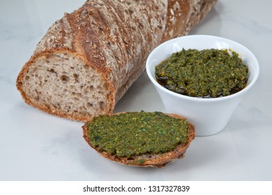 Wild garlic basil pesto in a white bowl and on a piece of bread together with a sliced baguette on a light background