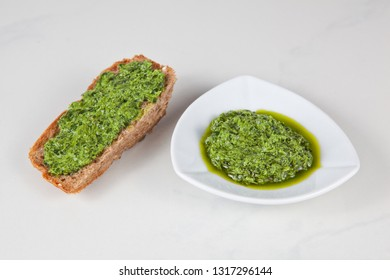 Wild garlic pesto in a white bowl and on a piece of toasted bread on a light background