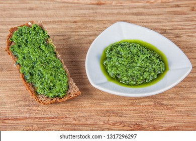 Wild garlic pesto in a white bowl and on a piece of toasted bread on a wooden background