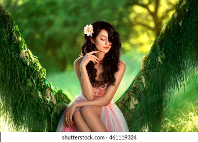 wild  girl in pale pink dress, with black curls sitting in the grass in the middle of the jungle. Hammock made of grass and flowers. Tropical woman with flower. Cute pretty face, creative color