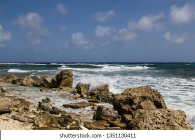 Wild and high waves rooling in at the rough and rocky shoreline of the east coast of the island of Bonaire in the caribbean