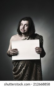 Wild man neanderthal in leopard skin hold empty paper sheet.