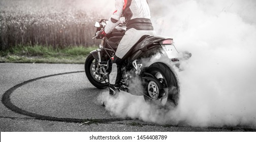 wild motorcyclist lets the tires spin during a burnout and makes a donut